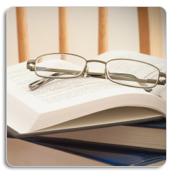 image of a pair of glasses on a pile of school books