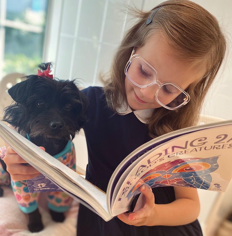 a girl reading with her dog